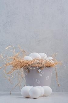Oeufs blancs frais dans un seau sur fond de marbre.
