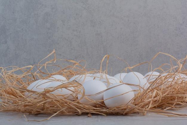 Oeufs blancs frais sur fond de marbre.