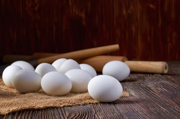 Oeufs blancs sur toile de jute et table en bois. en arrière-plan, un rouleau à pâtisserie rustique. discret.