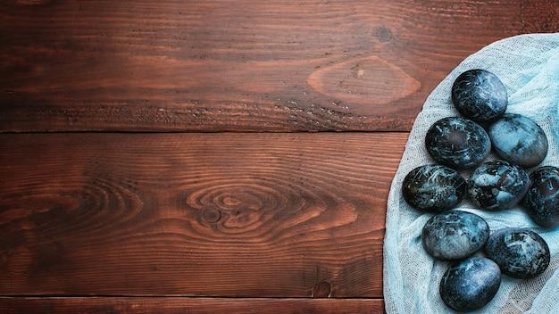 Oeufs bleus texturés peints pour la célébration de pâques sur tissu sur fond de bois