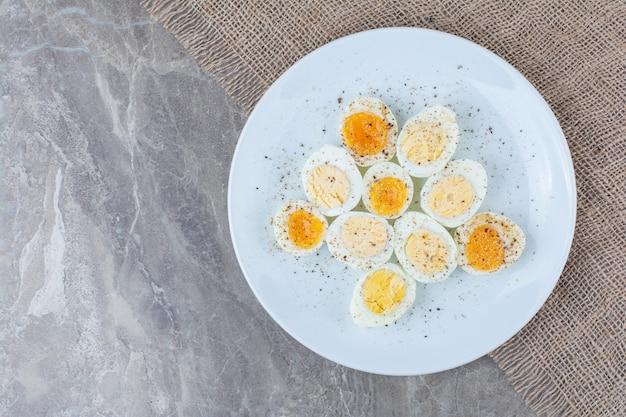 Oeufs bouillis savoureux avec des épices sur une plaque blanche. photo de haute qualité
