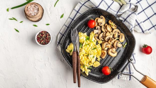 Œufs brouillés aux champignons. délicieux petit-déjeuner ou collation sur une table lumineuse.