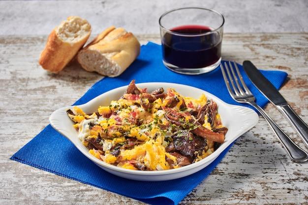 Œufs brouillés aux champignons et jambon ibérique avec pain et vin rouge