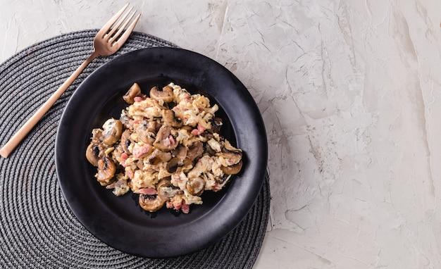 Oeufs brouillés aux champignons et jambon. plat espagnol. copie espace