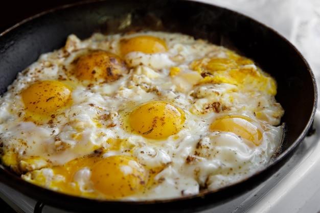 Les œufs brouillés aux épices sont cuits dans une poêle.