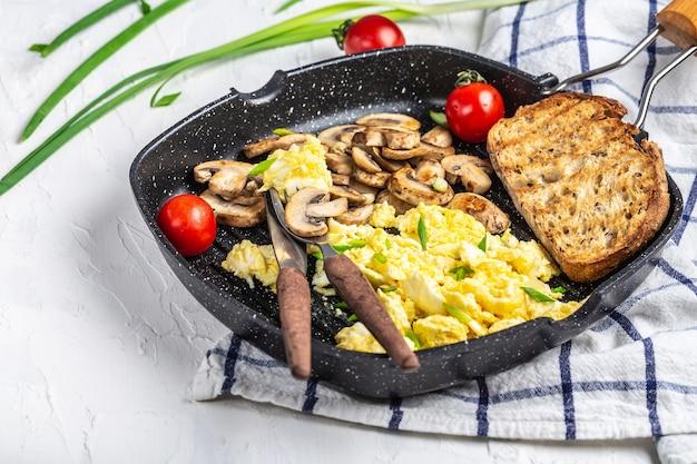 Oeufs brouillés aux oignons et champignons dans une poêle en fer à frire, tableau des recettes alimentaires. espace pour le texte. vue de dessus.