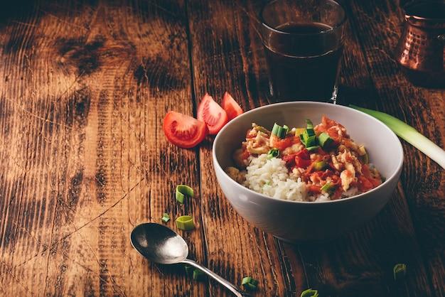 Œufs brouillés aux tomates, poireaux et riz blanc. café turc et ingrédients tranchés.