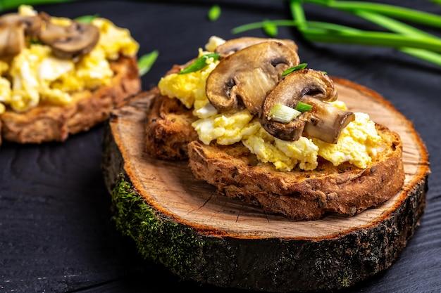 Œufs brouillés et champignons sur des toasts de blé entier. petit-déjeuner ou brunch santé.