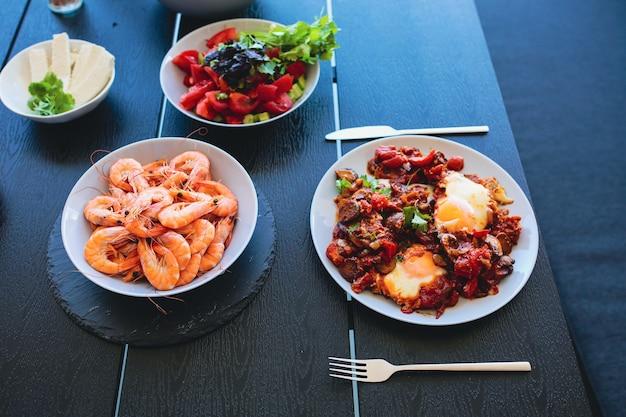 Oeufs brouillés cuits avec salade shakshuka servant sur la terrasse d'été petit-déjeuner à l'extérieur frit