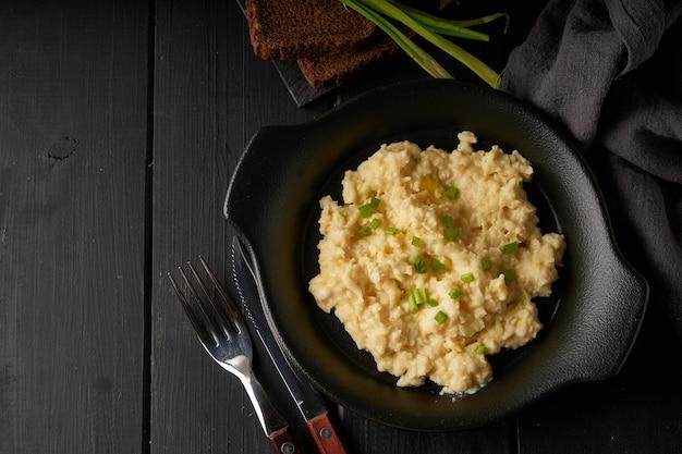 Oeufs brouillés à l'oignon vert servi dans une assiette sombre avec du pain sur la table