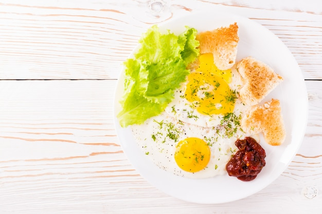 Oeufs brouillés, pain frit, ketchup et feuilles de laitue sur une assiette sur la table