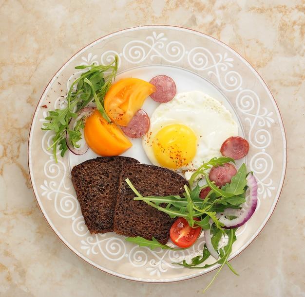 Œufs brouillés avec saucisse, légumes verts et pain grillé