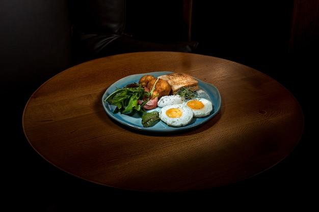 Oeufs brouillés sur la viande avec pommes de terre frites et toasts