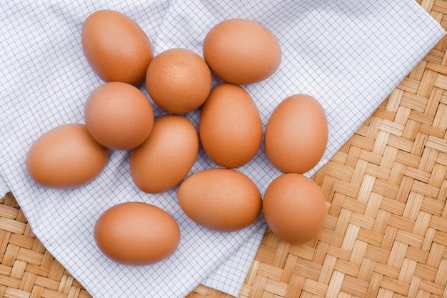 Des œufs bruns pondent sur un tissu à carreaux blanc. concepts d'aliments sains.