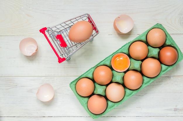 Œufs bruts de poulet brun dans une boîte en carton vert et un panier d'achat