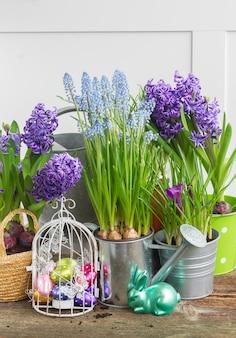 Oeufs en cage à oiseaux et lapin avec pots de fleurs et fleurs
