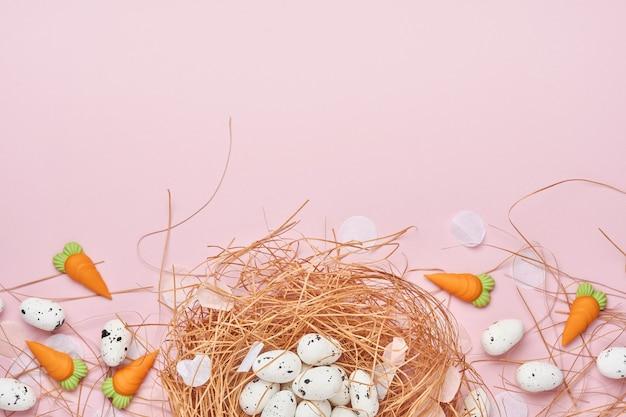 Oeufs de caille au nid et carotte sucrée sur table rose. composition horizontale créative minimale de pâques avec espace de copie. printemps joyeuses pâques vue de dessus.