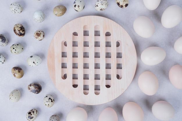 Œufs de caille bio et œufs de poule sur une surface blanche.