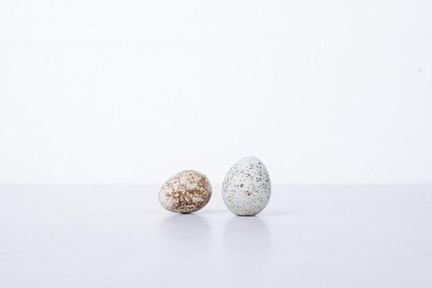 Œufs de caille bio sur une surface blanche.