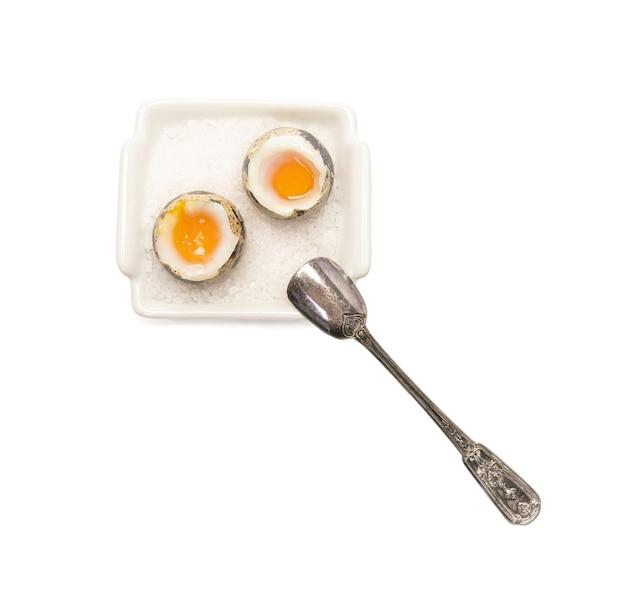 Oeufs de caille bouillis dans un petit plat sur fond blanc