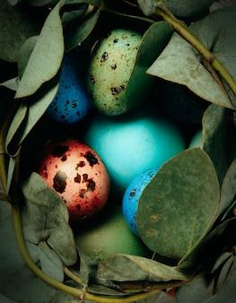Oeufs de caille colorés dans un nid de feuilles se bouchent