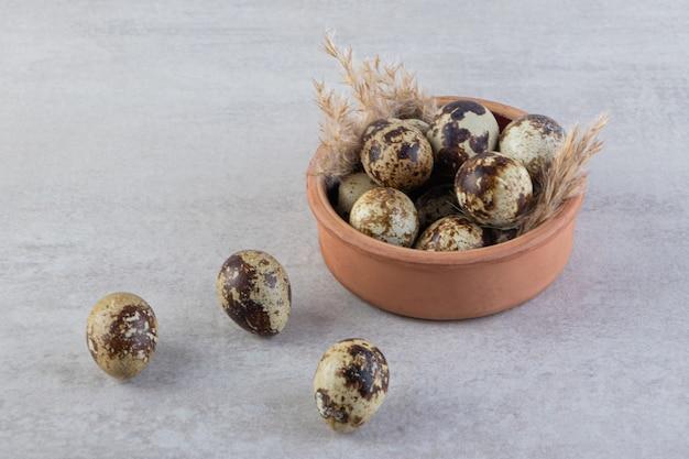 Œufs de caille crus frais entiers avec des épis de blé placés sur une table en pierre.