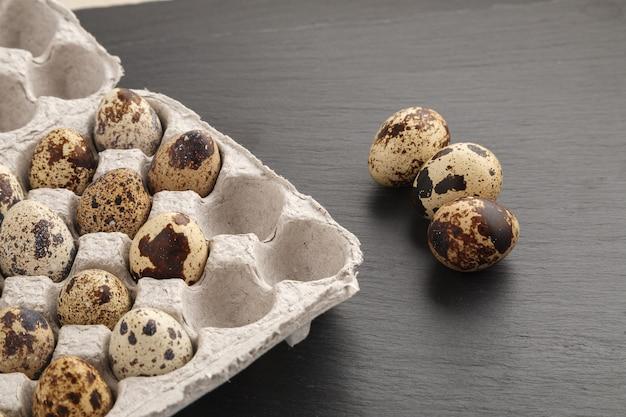 Oeufs de caille dans une boîte en carton sur la table gris pierre