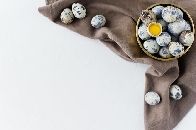 Œufs de caille dans un bol doré, un œuf cassé.