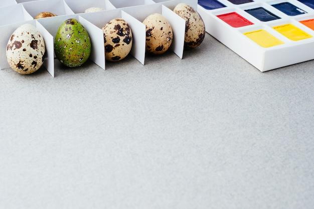 Oeufs de caille dans une grille et un oeuf de pâques peint sur fond gris. concept créatif de pâques, espace de copie. préparation traditionnelle pour pâques.