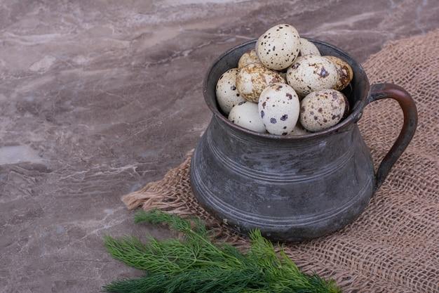 Œufs de caille dans un pot métallique avec des herbes