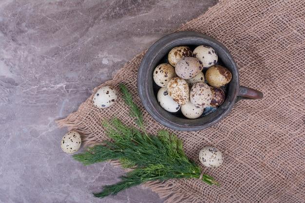 Oeufs de caille dans un pot métallique sur morceau de toile de jute.