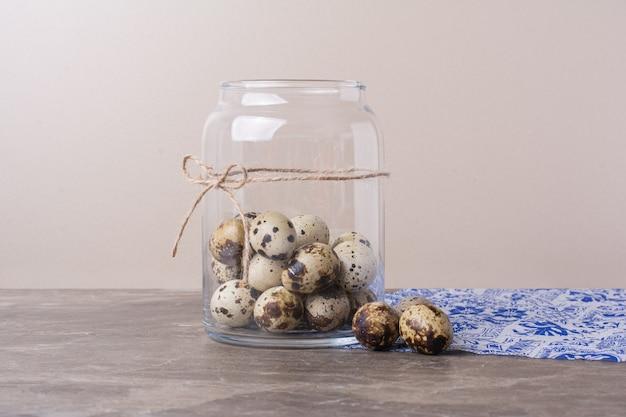 Oeufs de caille dans un récipient en verre sur marbre.