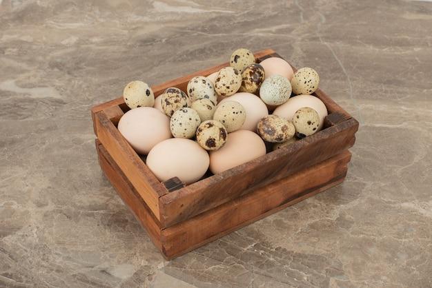 Oeufs de caille de ferme frais, crus sur une surface en marbre
