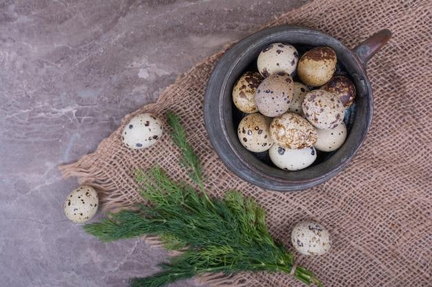 Oeufs de caille et herbes dans une tasse en bois.