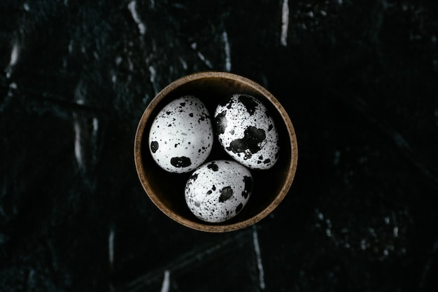 Oeufs de caille. oeufs de caille crus dans un récipient. trois oeufs de caille sur fond noir