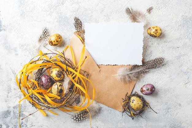 Oeufs de caille de pâques colorés jaune et violet avec des plumes dans de petits nids et carte de voeux dans une enveloppe. faible profondeur de champ. vue de dessus.