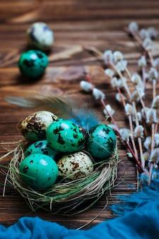 Oeufs de caille peints dans un nid naturel avec des branches de saule sur fond en bois rustique