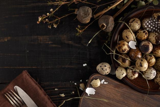 Oeufs de caille sur une plaque d'argile sur une surface en bois sombre.