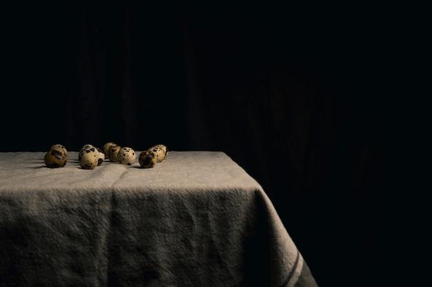 Œufs de caille sur la serviette entre la noirceur