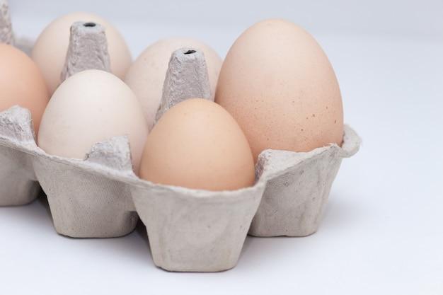 Œufs en carton, le plus gros parmi un autre petit œuf sur fond blanc. concept principal, leader, important.