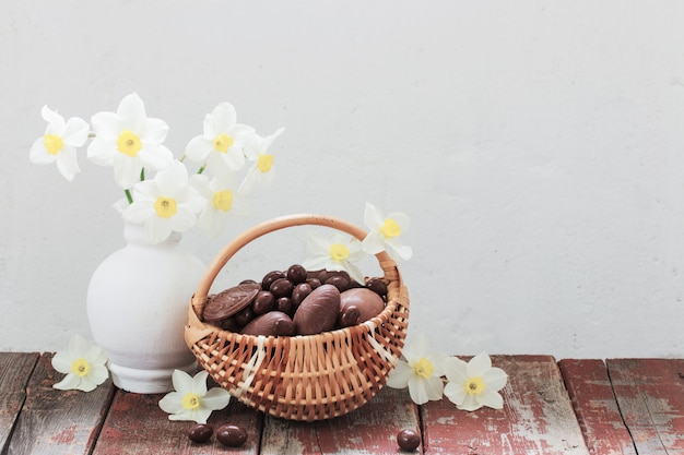 Oeufs en chocolat de pâques dans le panier et fleurs de printemps sur une vieille table en bois