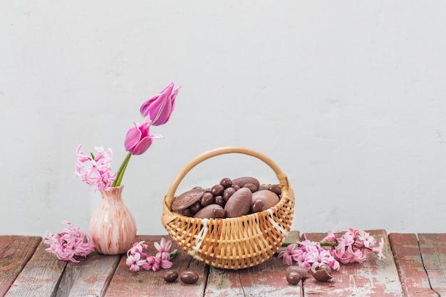 Oeufs en chocolat de pâques dans le panier et fleurs roses sur une vieille table en bois