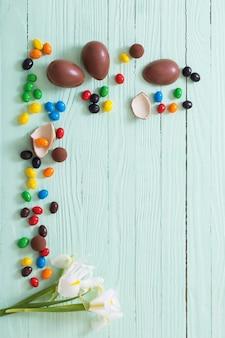 Oeufs en chocolat de pâques et fleurs sur fond de bois vert