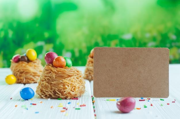 Oeufs en chocolat peints dans des nids douces avec carte vide