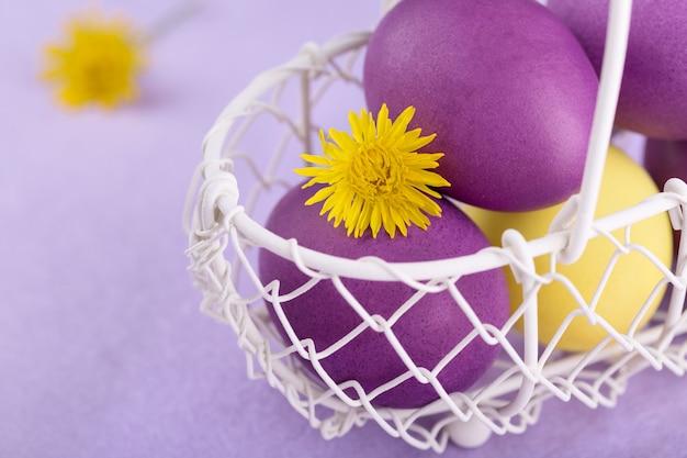 Oeufs colorés dans un panier blanc sur lilas