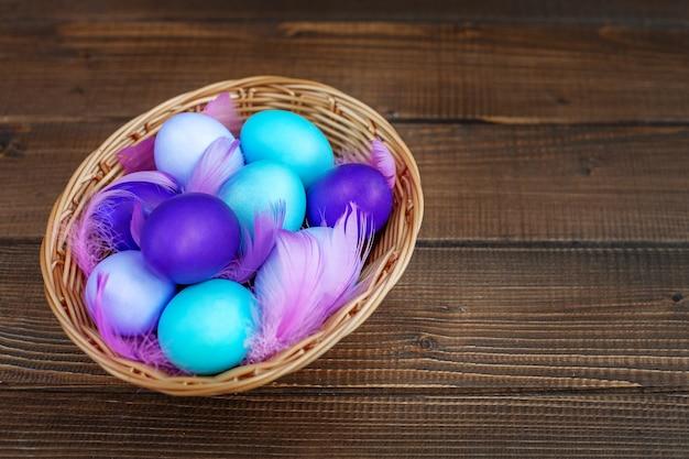 Oeufs colorés dans un panier en osier. concept joyeuses pâques.
