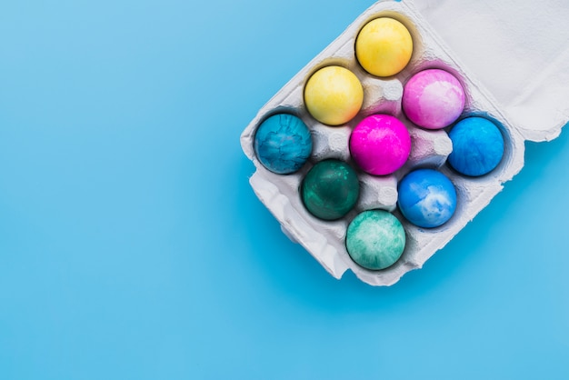 Oeufs colorés dans un porte-cartons sur fond bleu