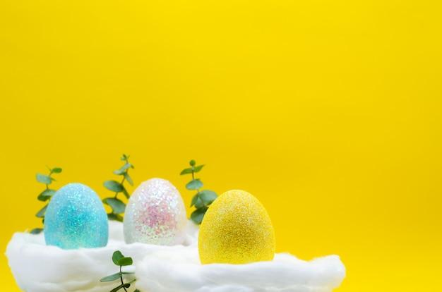 Des oeufs colorés décorent de paillettes pour le jour de pâques et le festival est placé dans le nid.