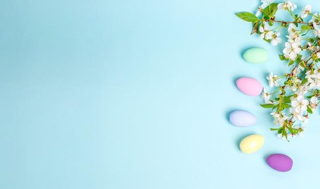 Oeufs colorés de pâques avec des branches de fleurs de cerisier sur fond bleu avec espace de copie. concept de saisonnalité, printemps, carte postale, vacances. mise à plat, place pour le texte. vue d'en-haut