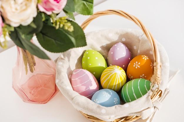Oeufs colorés de pâques en busket sur table en bois blanc. bouquet de fleurs roses sur table. joyeuses pâques. humeur printanière.
